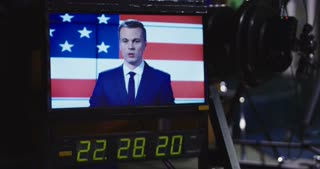 Screen on a monitor in a recoding studio showing a news presenter in front of a National flag with elapsing time below during production and filming. 4K shot on Red cinema camera