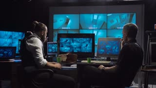 Security guards eating donuts while watching the surveillance cameras on screen while working late at night in an office with modern equipment