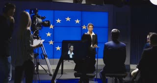 Serious African-American representative of European Union answering questions of journalists on news conference in semilit studio with EU flag on screen. 4K shot on Red cinema camera