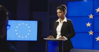 Serious African-American representative of European Union answering questions of journalists on news conference in semilit studio with EU flag on screen