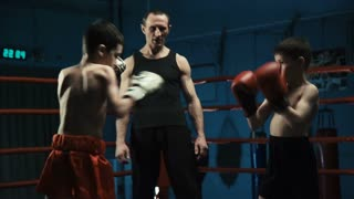 Serious coach watching boys in gloves boxing and practicing Thai box in gym training together.