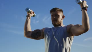 Serious tattooed man lifting metal dumbbells and exercising shoulder muscles looking determined against big blue sky