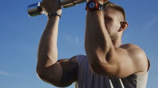 Serious tattooed man lifting metal dumbbells and exercising shoulder muscles looking determined on green summer field