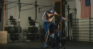 Shirtless brutal athlete sitting on air bike and cycling fast while working out in gym.