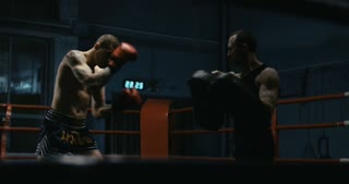 Shirtless muscular boxer with tattooed body working out on ring in gym attacking coach with punching bags.