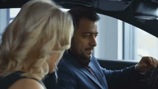 Side view of adult elegant man and woman sitting inside of new car in dealer shop and exploring all advantages. Movement stabilized 4k shot.