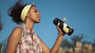 Side view of African young girl drinking water and pouring herself in summer heat while traveling. Slow motion