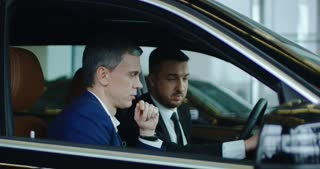Side view of agent pressing buttons on dashboard while showing options to adult businessman in new car. Slow motion. Shot on Red cinema camera