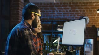 Side view of bearded man in glasses and beautiful asian woman surfing Internet and looking through web sites with concentration