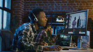 Side view of black man in headphones working on computer and editing video with color correction