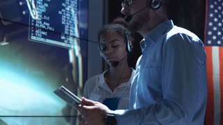 Side view of black woman and white man communicating in Moon mission control center. American flag on background