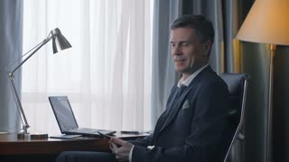 Side view of confident adult man in suit sitting at desk in elegant room with laptop and smartphone smiling at camera.