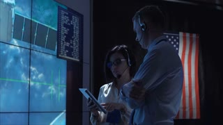 Side view of man and woman communicating in space flight control center. Some elements of this image furnished by NASA