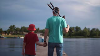 Side view of man holding hand of son and looking at camera with rods on shoulder