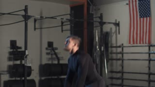 Side view of man in black sportswear doing exercise with weight bag lifting it up and down in gym.