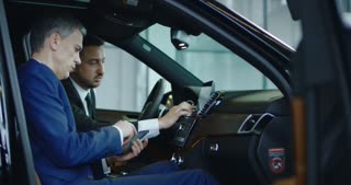 Side view of manager and businessman connecting smartphone to car computer in showroom