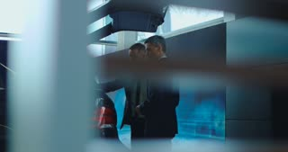 Side view of manager in suit showing car trunk size to adult businessman in showroom