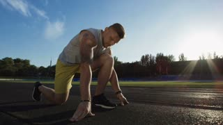 Side view of strong tattooed athlete setting off to run from crouch start position on sunny racetrack of stadium