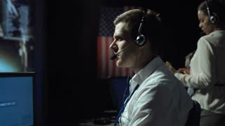 Side view of supervisor man in headset sitting and working in space mission control center. Moon Landing