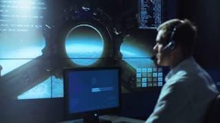 Side view of supervisor man in headset sitting and working in space mission control center