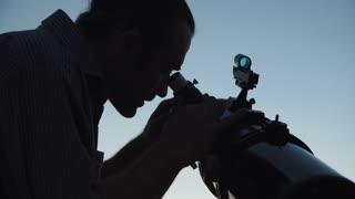 Silhouette of man looking through telescope
