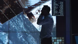 Silhouette of supervisor man standing near big screen in space flight control center watching satellite. Elements of this image furnished by NASA