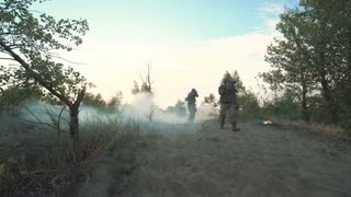 Silhouettes group of military men running on field in smoke and falling killed. Under mortar shelling