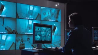 Single female security person monitoring closed circuit surveillance from multiple cameras