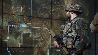 Single male bearded soldier in camouflage army uniform reviewing monitor of missle launch on large computer screen display