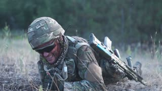 Slow motion man in military uniform with gun crawling alone on ground in field