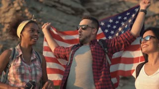 Slow motion multiracial group of people embracing and posing with American flag on coast while traveling