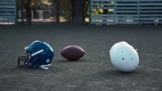 Slow motion of American football players preparing protective helmets before game on field