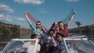 Slow motion of diverse group of excited people sailing on boat playing with colored smoke bombs and celebrating Independence day