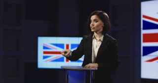 Slow motion of female news anchor presenting British news pointing and gesturing with her hand as she speaks standing behind a small podium. 4K shot on Red cinema camera