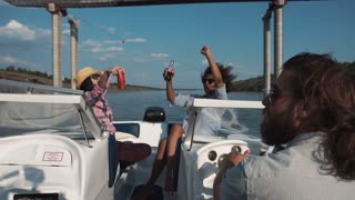 Slow motion of group of diverse happy women relaxing on board a motor boat as they approach a bridge along a river laughing and cheering waving their beers in the air