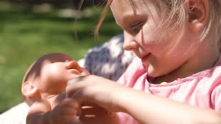 Slow motion of little girl relaxing in armchair in garden playing and feeding baby doll