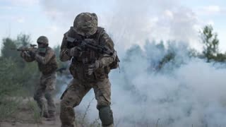 Slow motion of soldiers on battlefield and aiming with guns. The soldier is wounded and he is saved by other soldiers covering