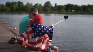 Slow motion of son raise American flag while his dad make self picture using cell phone mounted on monopod or selfie stick