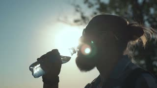 Slow motion shot of side view of stylish man with ponytail drinking water from bottle on background of sunlight and nature