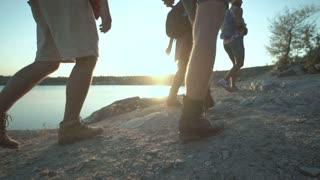 Slowmotion of anonymous group of multiethnic people with backpacks walking on rocky shore in sunlight while hiking