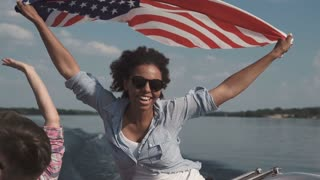 Slowmotion of cheerful African American female holding US flag on boat celebrating Independence day and having fun