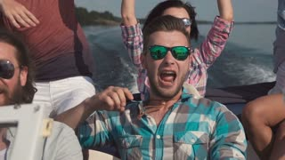 Slowmotion of emotional group of mixed ethnic young friends on board a motor boat along a river laughing and cheering and raise american flag in air. Celebrate an Independence Day on July 4