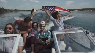 Slowmotion of group of cheerful friends on boat celebrating Independence day and having fun