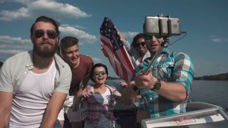 Slowmotion of group of laughing friends having fun on boat and taking selfie