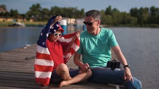 Slowmotion of mature man and boy sitting on pier and holding American flag while laughing and grimacing and make self photo using smartphone mounted on selfie stick