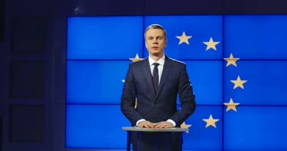 Smart male news anchor presenting European news standing in front of the EU flag speaking panning slowly to the left Shot on Red cinema camera