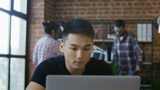 Smart young Korean man working at table with computer looking serious and concentrated