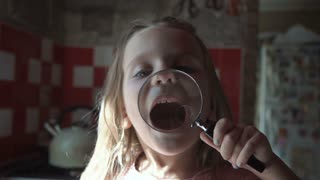 Smiling little girl playing and grimacing with loupe on kitchen