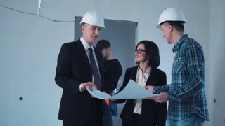 Smiling professionals looking into the blueprint and shaking hands