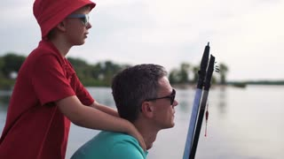 Son embracing father holding rod on background of pier